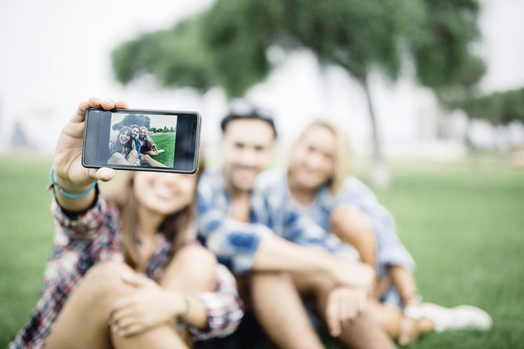 Young woman with friends taking selfie on field