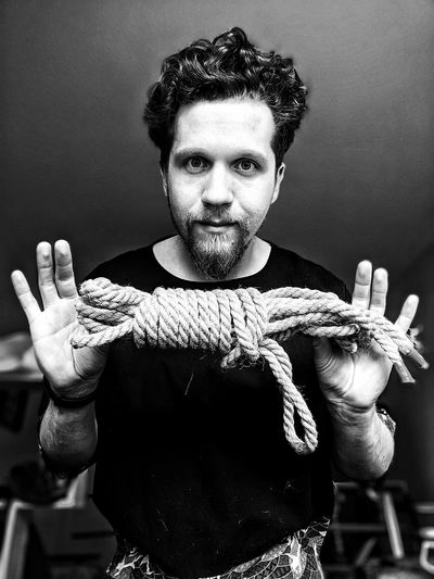 Portrait of young man with rope standing against wall