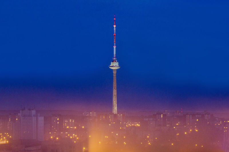 Communications tower in illuminated city at night