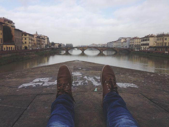 Low Section Of Man Resting By Ponte Santa Trinita Against Sky