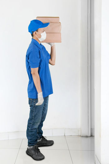 Full length of delivery person wearing mask standing by door