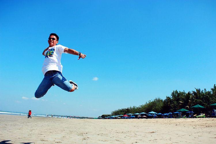 Rear view of woman jumping at beach