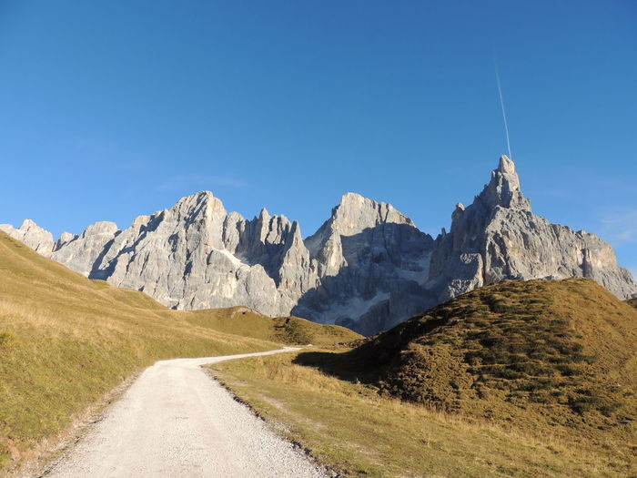 Low angle view of footpath leading to rocky mountains