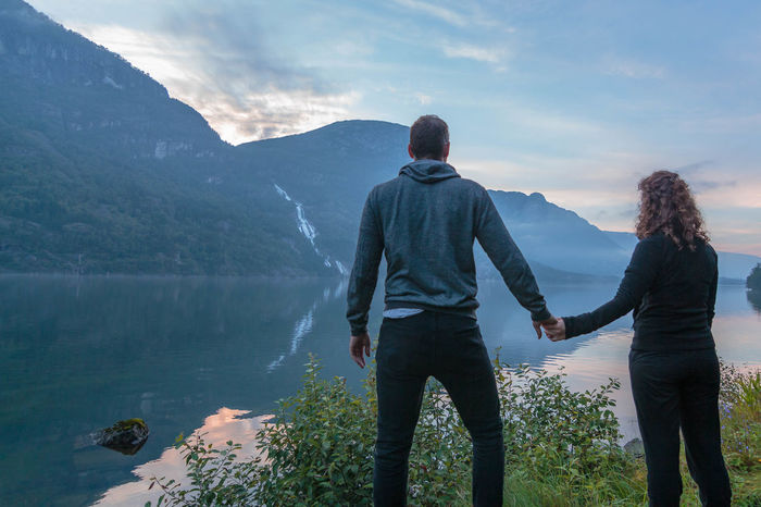Beauty In Nature Casual Clothing Cloud - Sky Getting Away From It All Idyllic In Front Of Lake Leisure Activity Lifestyles Majestic Men Mountain Mountain Range Nature Non-urban Scene Person Rear View Scenics Sky Standing Togetherness Tranquil Scene Tranquility Watching The Sunset Water