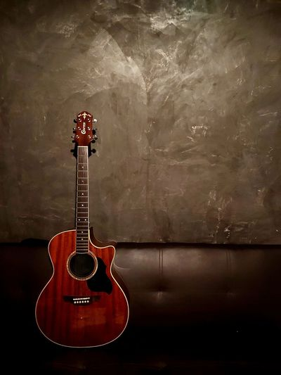 Close-up of guitar on table against wall
