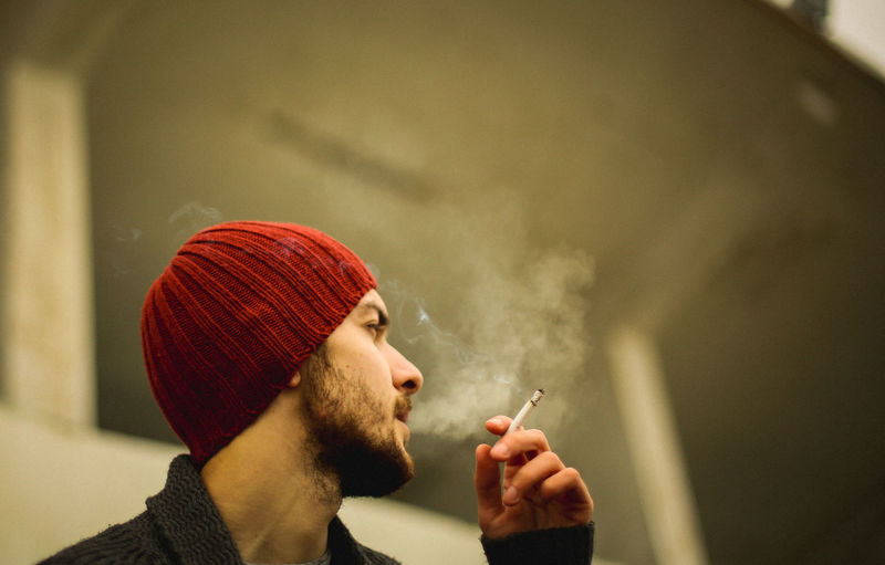 Low angle view of young man smoking cigarette outdoors