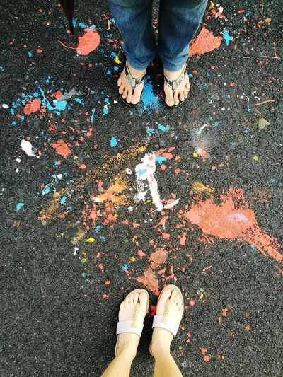 Low Section Of Friends Standing On Road With Paints
