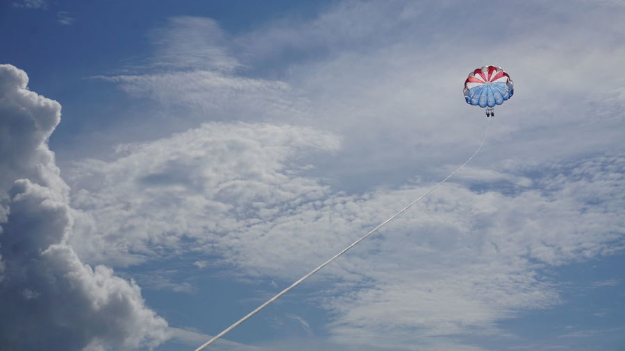 Low angle view of two people parasailing against cloudy sky