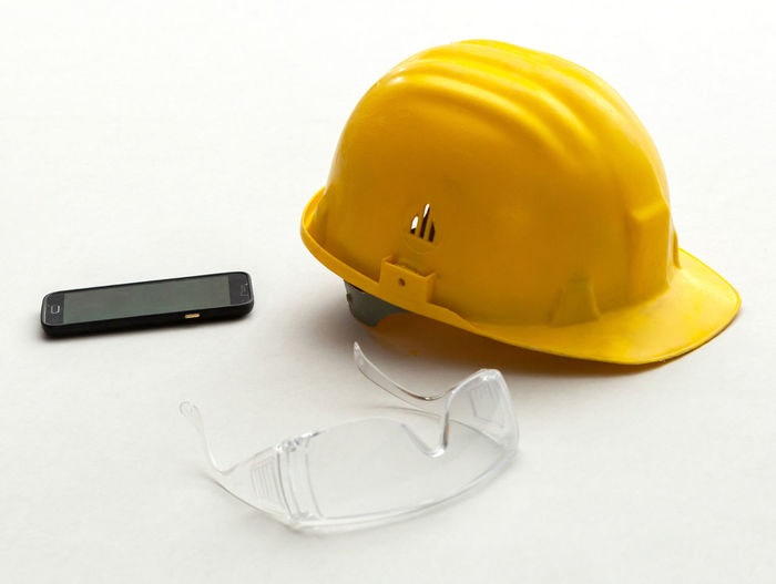 Close-up of hardhat with eyeglasses and mobile on white background
