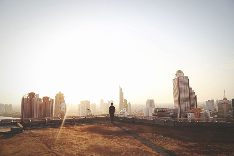 Person standing on roof of building with city skyline in background