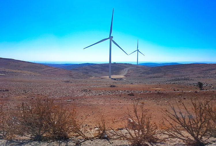 Wind turbines on desert land against blue sky