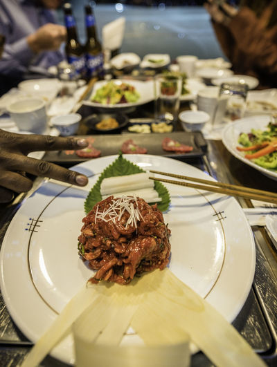 raw beef tartare in Korean restaurant Food And Drink Food Plate Table Ready-to-eat Wellbeing Freshness Meat Meal Close-up Hand Human Hand Selective Focus Dinner Asian Food Korean Food Restaurant Beef Tartare Beef Raw Food Gettogether Glass High Angle View Banchan Seoul