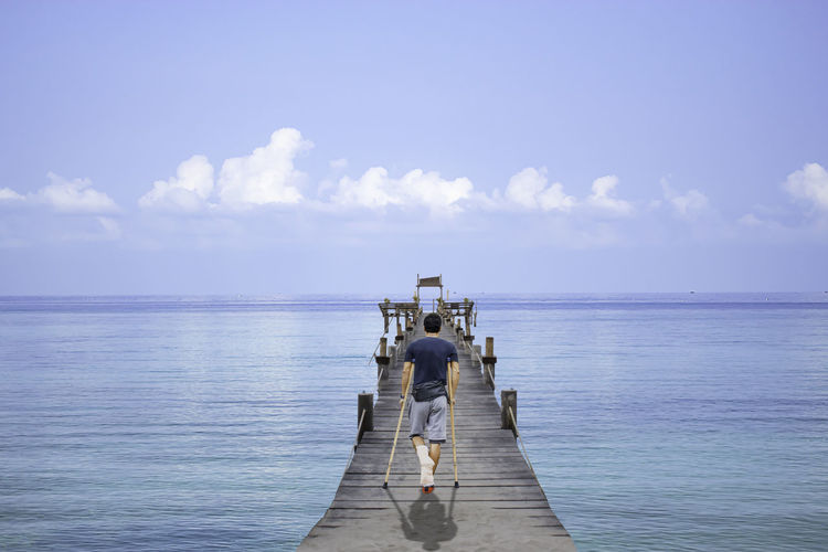 Rear view of man with crutches walking on pier over sea against sky