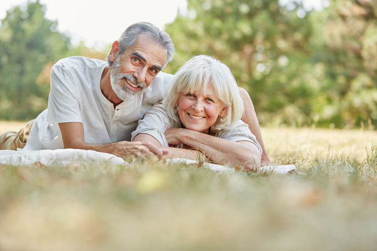 Portrait Of Smiling Couple Lying On Field At Park