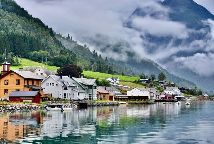 Calmness World Travel Wanderlust Idyllic Fjord Travel Photography Peaceful View Serene Outdoors Norway Village Water Building Exterior Built Structure Architecture Building House Mountain Waterfront Cloud - Sky Beauty In Nature Nature Reflection Scenics - Nature Outdoors
