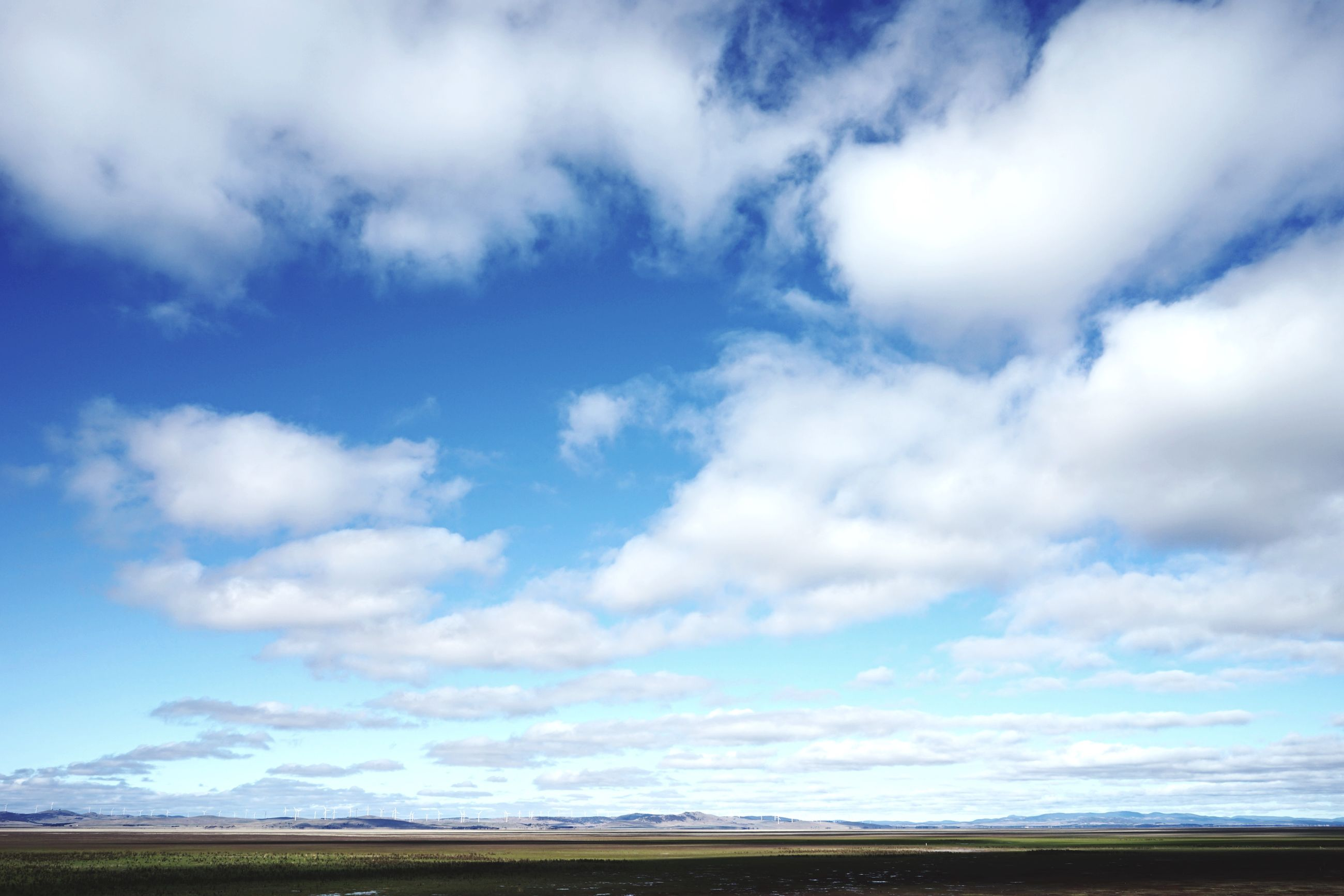 sky, tranquil scene, tranquility, landscape, scenics, cloud - sky, beauty in nature, cloud, nature, field, blue, cloudy, horizon over land, non-urban scene, idyllic, remote, day, outdoors, no people, solitude
