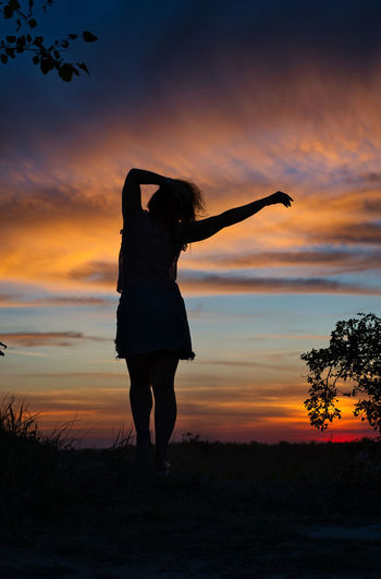 Silhouette woman standing on land against sky during sunset