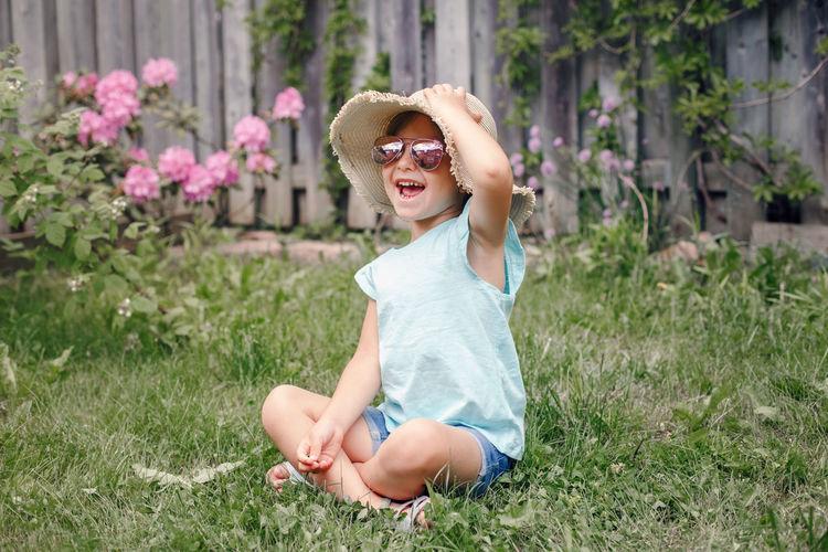 Smiling girl sitting in grass at yard