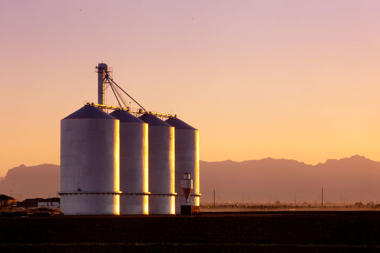 Silo on lands against sky during sunset
