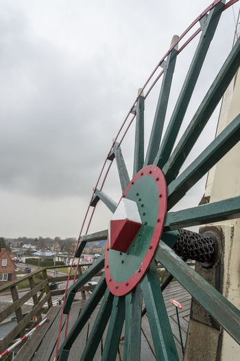 Steering Wheel of a windmill Windmill Architecture Building Exterior Built Structure Close-up Cloud - Sky Connection Day Focus On Foreground Metal Mode Of Transportation Nature No People Outdoors Railing Red Rope Sky Steering Wheel Transportation Wheel