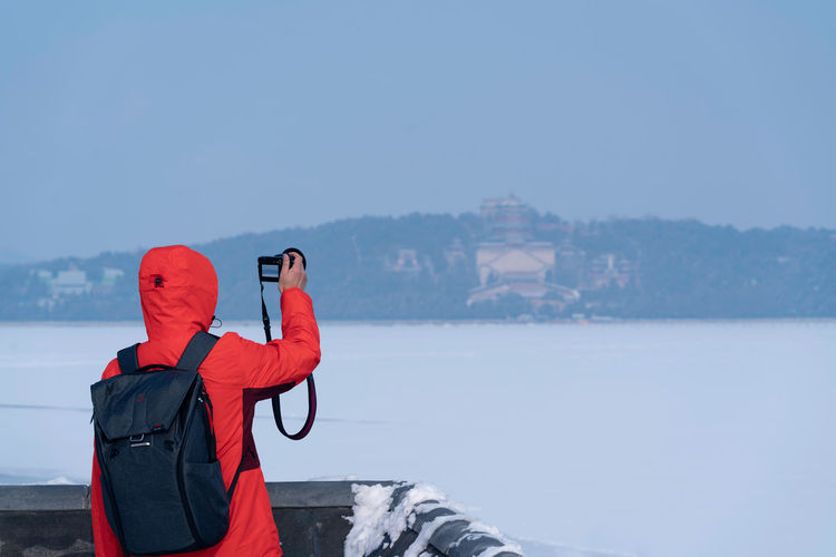 Rear view of person standing by sea against sky during winter