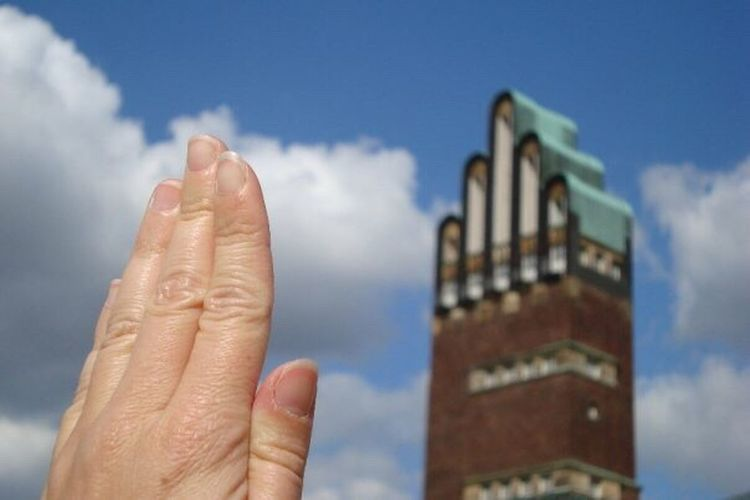 Close-up of cropped hand against the sky