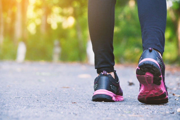Low section of woman wearing sports shoe while standing outdoors
