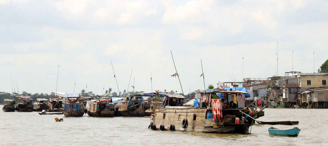 Boats moored on mekong river against cloudy sky