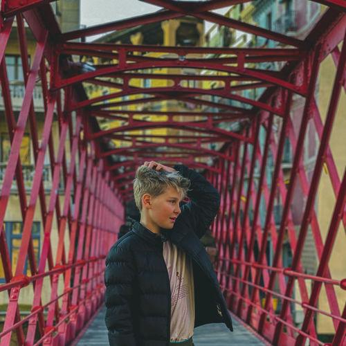 Man standing on bridge in city