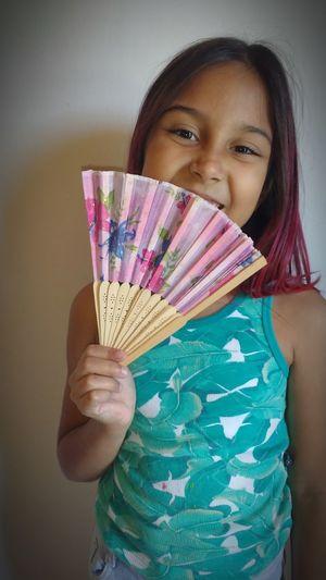 Portrait of happy girl holding folding fan against white wall
