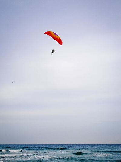 Distant view of person paragliding over sea against sky