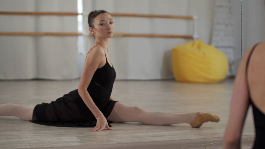 Ballet dancer stretching against wall