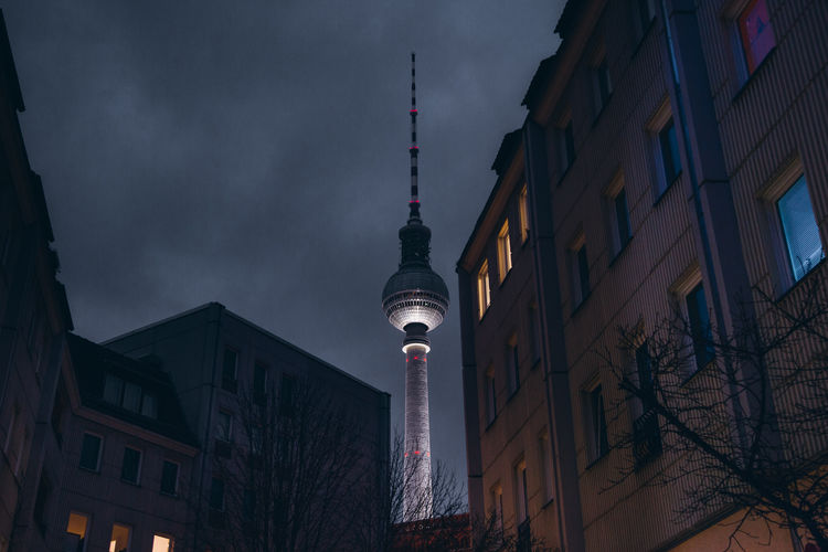 Low Angle View Of Fernsehturm By Buildings Against Sky In City At Night