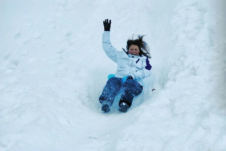 High Angle View Of Woman Sliding On Snow Covered Hill