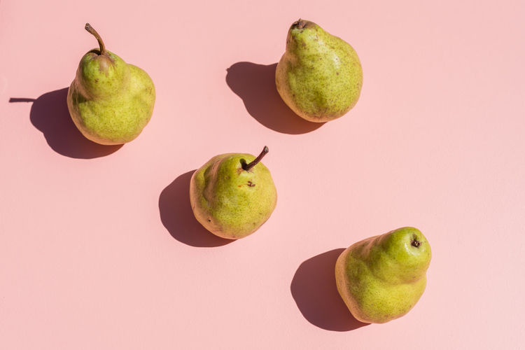 Pears on pink Fruit Food And Drink Healthy Eating Food Still Life Freshness Studio Shot Wellbeing Indoors  Green Color No People Close-up Apple Group Of Objects Pear Colored Background Cut Out Two Objects Ripe
