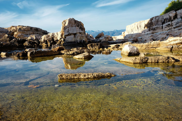 Scenic view of rock formation in lake against sky