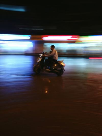 Man Riding Motor Scooter On Road At Night