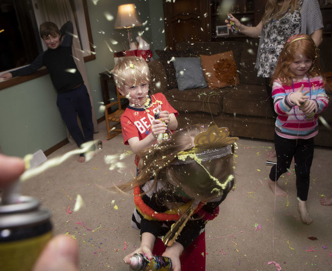 A family celebrates New Year's Eve at their home with silly string and confetti. Childhood Child Group Of People Girls Females Real People Women Family Innocence Lifestyles Toy Leisure Activity People Togetherness Celebration Casual Clothing Positive Emotion Daughter Celebration New Year's Eve Silly Family New Year's Eve 2019