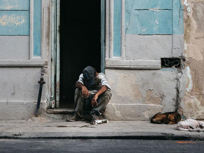 Man sitting on door of building