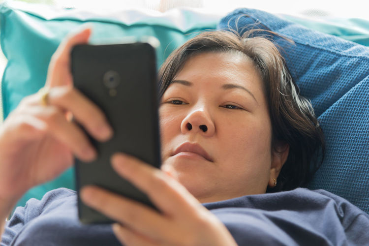 Mature woman holding mobile phone while lying on sofa at home