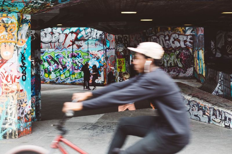Blur image of man riding bicycle against women standing by graffiti