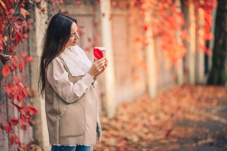 Midsection of woman holding umbrella standing during autumn