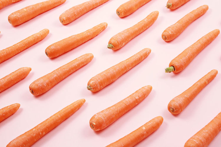 High Angle View Of Carrots Arranged On White Background