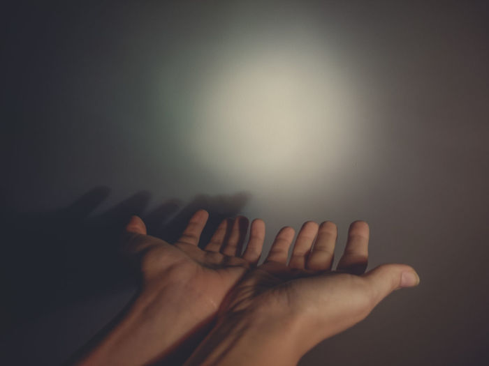 Cropped Image Of Woman Gesturing Against Light On Wall