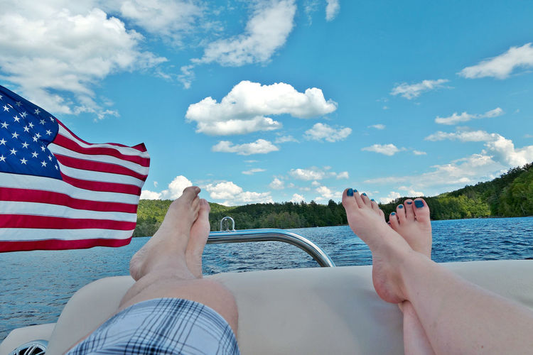 Relaxing on the lake with an American Flag waving. American Flag Beauty In Nature Boat Close-up Cloud - Sky Crossed Legs Day Human Body Part Human Leg Lake Landscape Lifestyles Men Nature Outdoors Patriotism People Pontoon Real People Scenics Sky Stars And Stripes Tree Water Women Sommergefühle