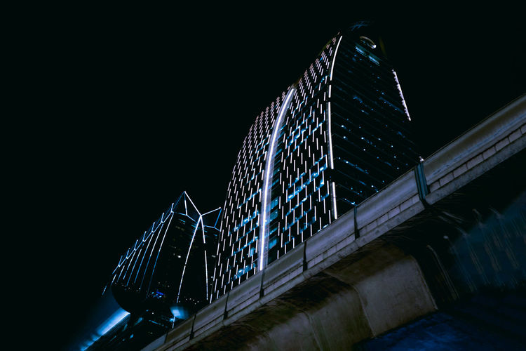 Low angle view of illuminated bridge against sky at night