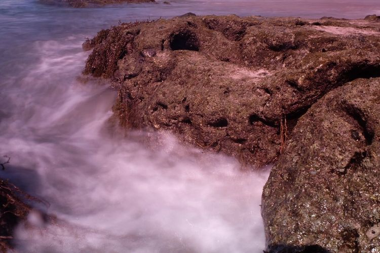 Close-up of rock formation in sea against sky