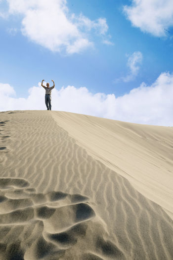 Low Angle View Of Senior Man Standing On Sand Dune Against Sky