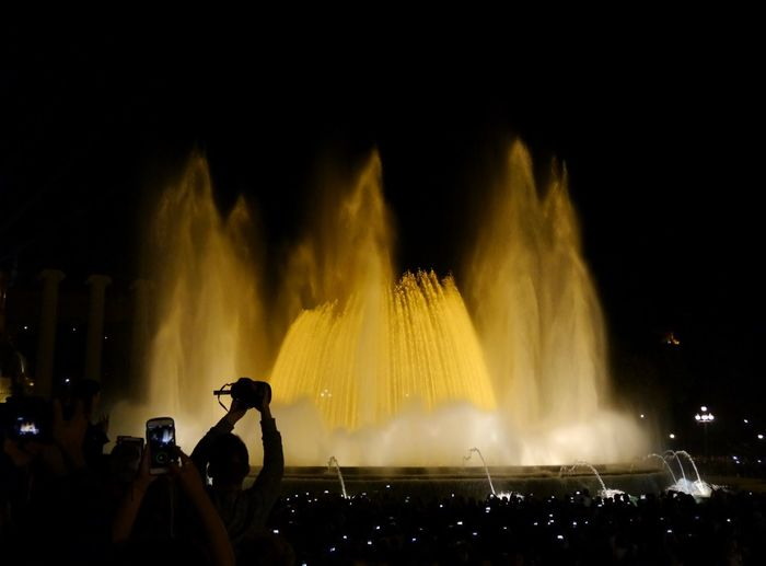 Taking photos from illuminated fountain Wireless Technology Photography Themes Arts Culture And Entertainment Mobile Phone Technology Performance Night Nightlife Filming Human Hand Eyem Gallery EyeEm Gallery Fountain Illuminated Yellow Light Large Group Of People Nightlife Travel Barcelona Magic Fountain Plaza España The City Light Mobile Conversations Welcome To Black The Street Photographer - 2017 EyeEm Awards Neighborhood Map Your Ticket To Europe Been There. Connected By Travel Stories From The City HUAWEI Photo Award: After Dark
