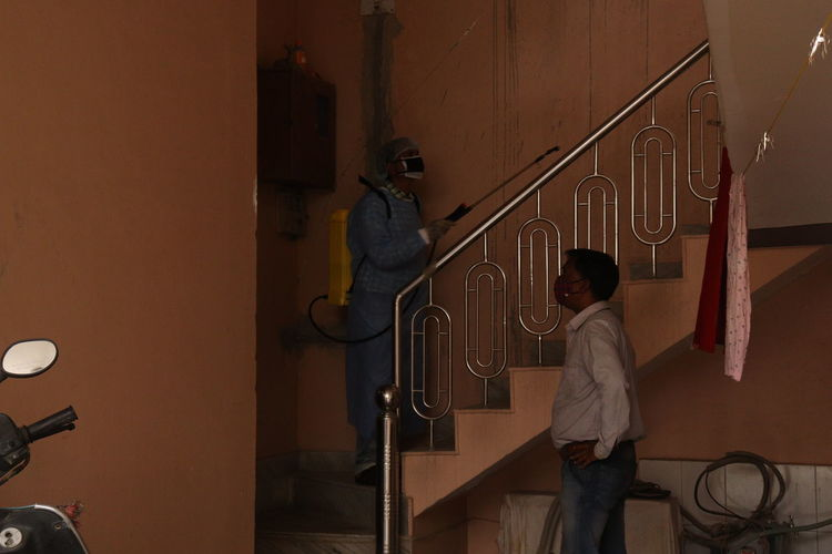 Rear view of men standing on staircase